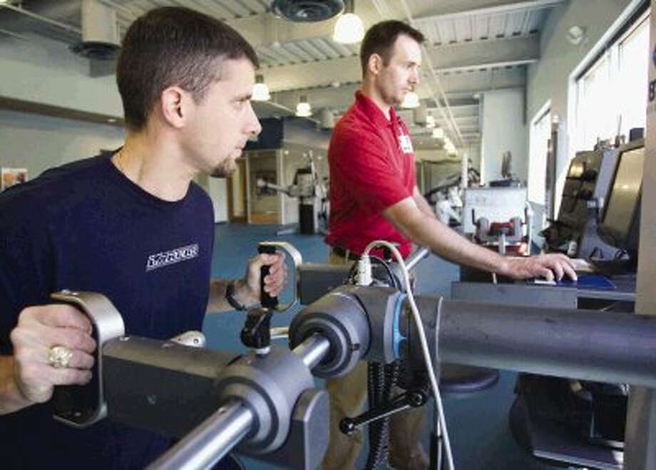 Jay Pierson, left, athletic development coach, demonstrates a machine that measures strength under the direction of Andrew Arthur, director of Clinical Services at the new 7,000-square-foot St. Luke's Performance Medicine Center. The new facility features equipment to help athletes train or recover from injuries as well as provide rehabilitation for patients who have suffered a medical condition such as a stroke. Photo: Staff Photo By Eric Swist