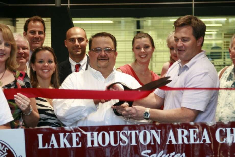 Bert Brocker, center, celebrated the completion of renovations and improvements at Humble's Texan GMC Buick with his staff and members of the Lake Houston Area Chamber of Commerce Sept. 12.