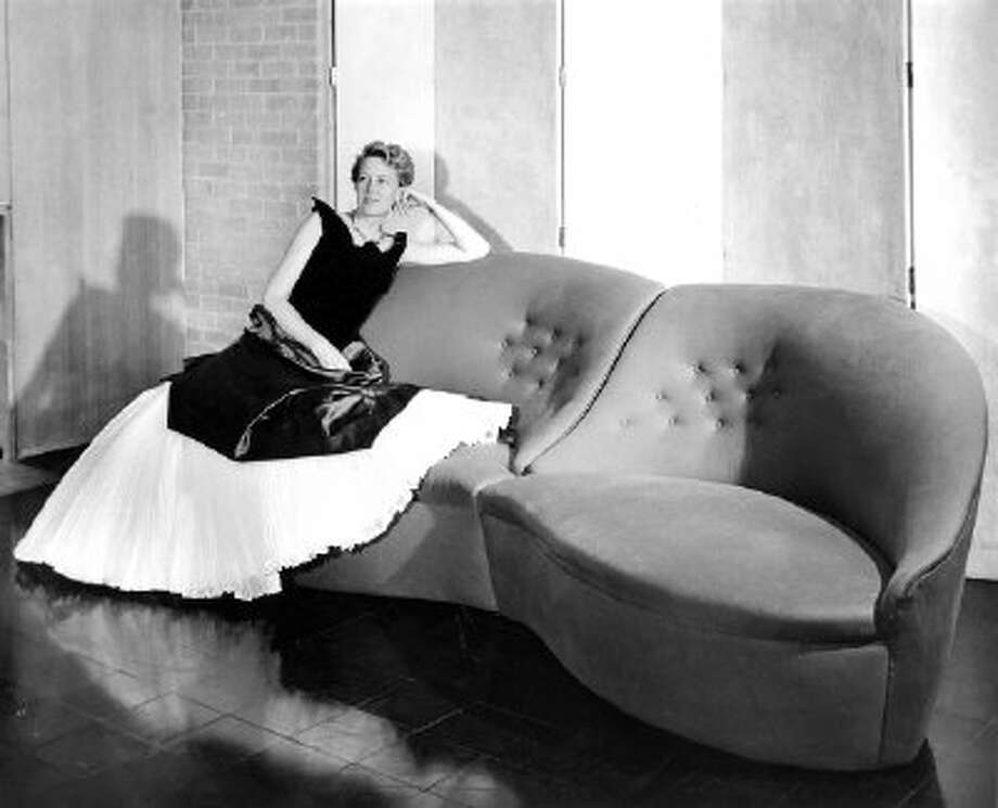 Dominique de Menil wearing a Charles James gown and seated on a sofa designed by James for the de Menils' home, ca. 1951.