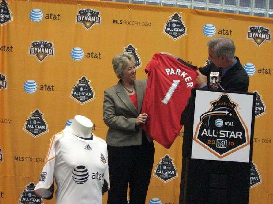 Oliver Luck, former Dynamo head, presents Houston Mayor Annise Parker with her own jersey in honor of the AT&T MLS All-Star Game on July 28.