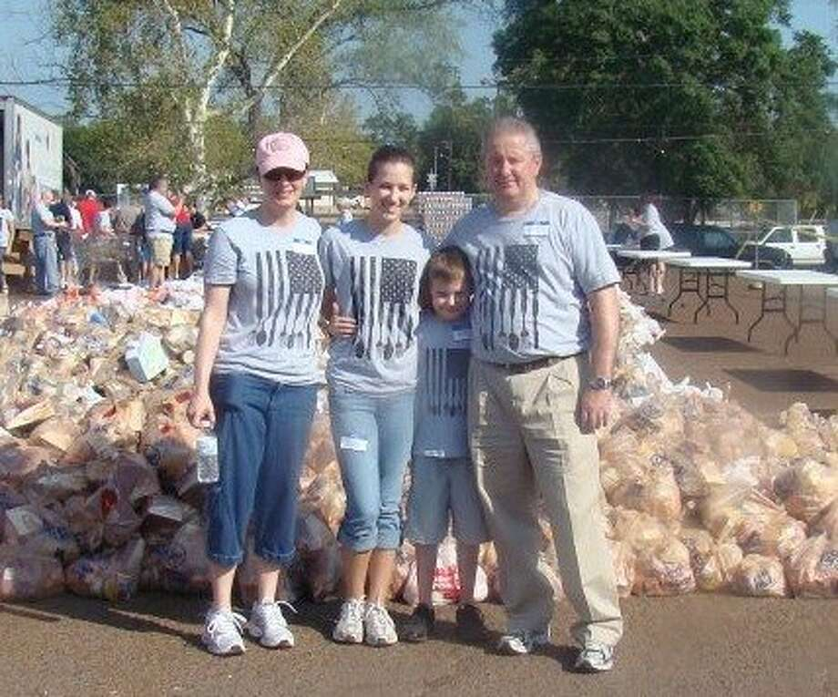 Terry and Amy Luker volunteer with their children, Katie and Michael, to help feed the hungry Community Christian Church has embarked on its third outreach event to feed the hungry, this time in the Magnolia area.