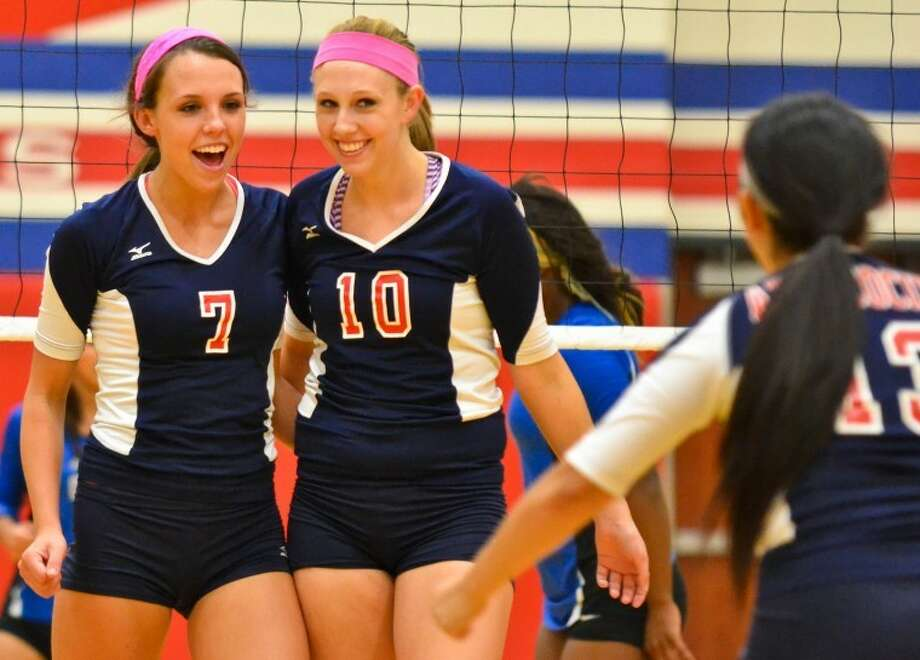 Jessica Wooten (7) and Angela Dunham (10) celebrate a point for Atascocita in the second game of the Lady Eagles' 3-0 win over Dekaney Sept. 18. Photo: Photo By Stephen Whitfield