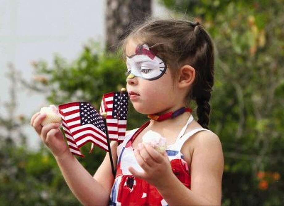 Camren Speer balances a pair of American flags while holding cupcakes during the Red, Hot and Blue Festival at Waterway Square in The Woodlands Thursday. Go to HCNPics.com to view and purchase this photo, and others like it. Photo: Staff Photo By Jason Fochtman / Conroe Courier
