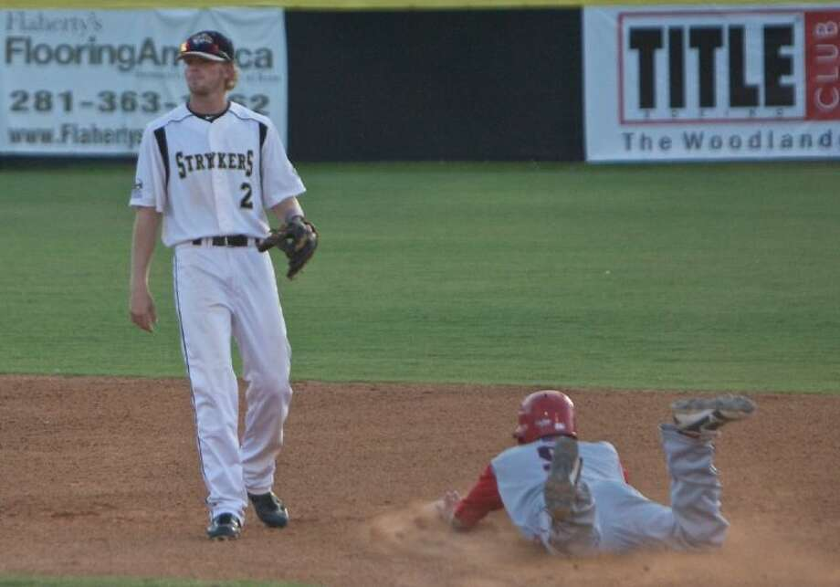 The Strykers' Conner Fikes looks on as the Cane Cutters' Kaleb Jon Fontenot slides into second base during Saturday night's game. Photo: Staff Photo By Eric Swist