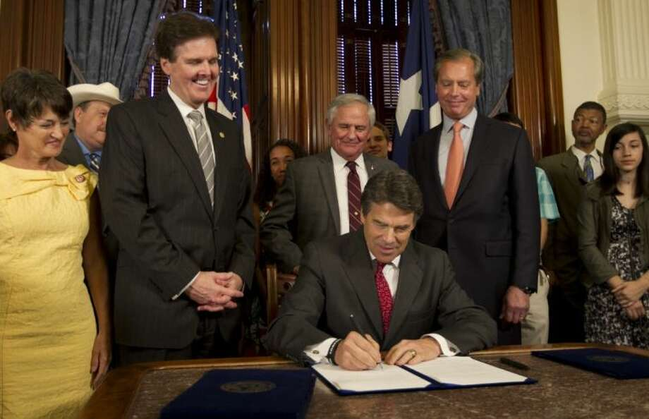 Gov. Rick Perry signs House Bill 5, which dramatically scales back testing in Texas, with the support of, left to right, Sen. Donna Campbell, Sen. Dan Patrick, Rep. Jimmie Don Aycock and Lt. Gov. David Dewhurst at the Governor's Public Reception Room at the Capitol in Austin June 10.