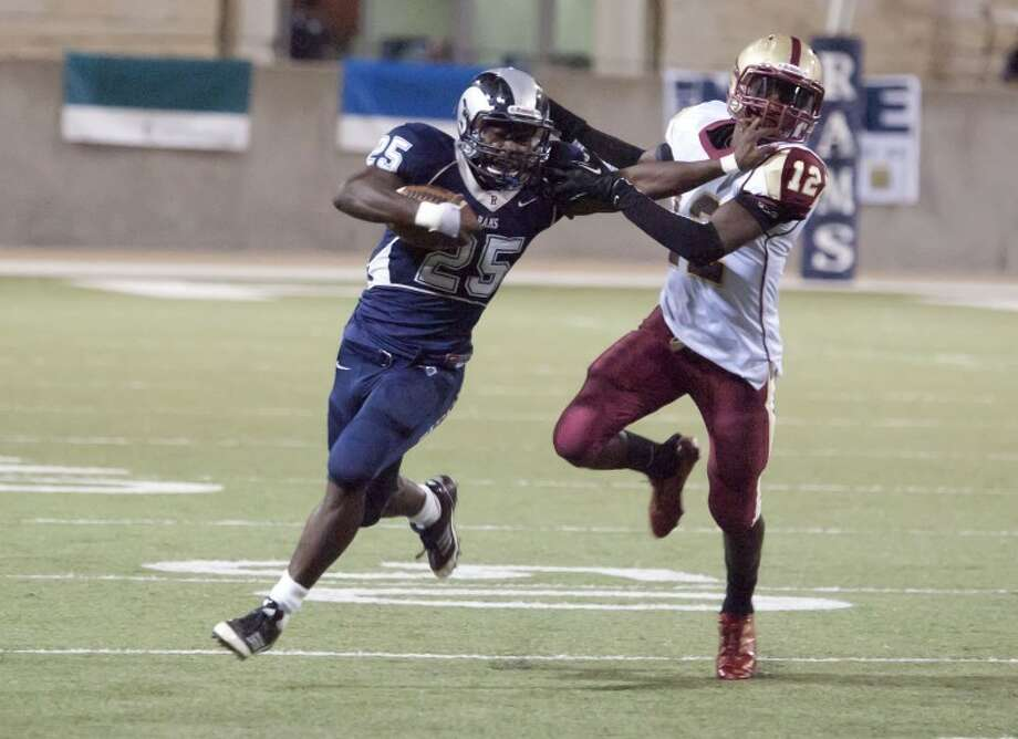 Cy Woods' Alfred Pullomattempts to take downCy Ridge's Rennie Childs during the two teams'game on Thursday at theBerry Center. Childs had 176 yards rushing in theRams' 54-21 win. Photo: Karl Anderson