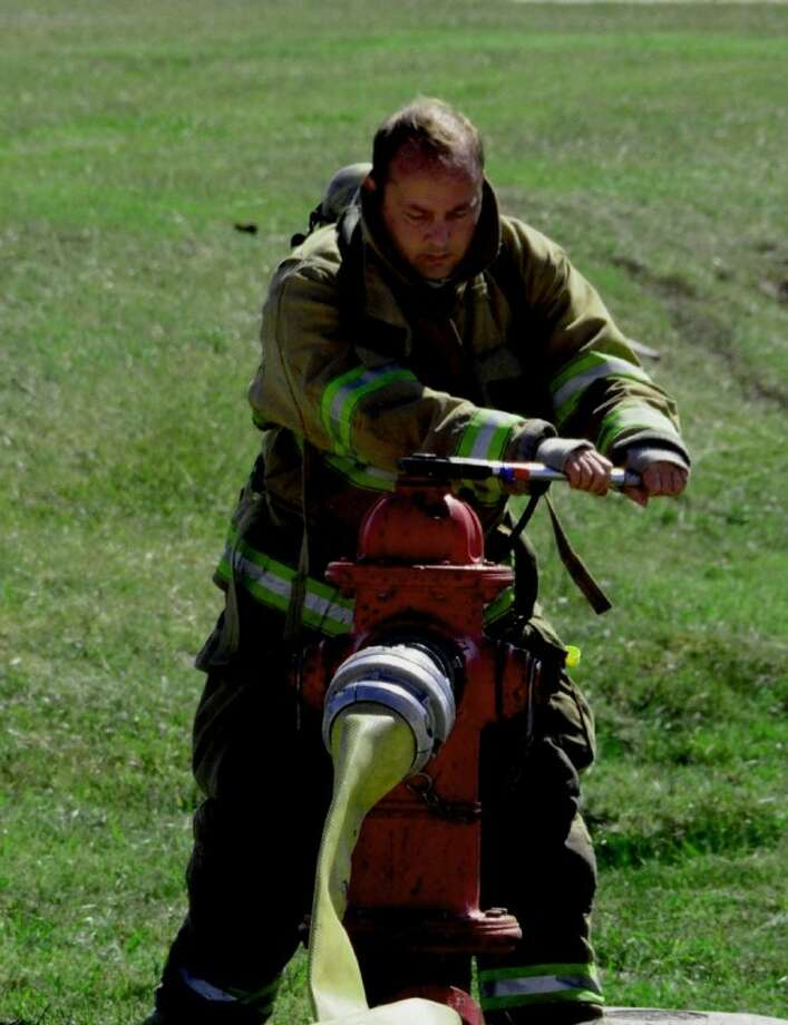 Capt. Neal Smith, during recruit training, working on a fire hydrant.
