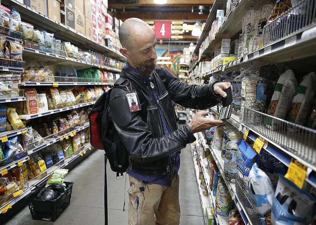 Customer David Skolnick tries to scan items on the Selfycart app at Rainbow in San Francisco.