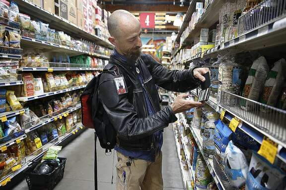 Customer David Skolnick tries to scan items on the Selfycart app at Rainbow on Monday, September 26, 2016, in San Francisco, Calif.   The Selfycart app allows people to scan codes on items they wish to buy, then lets them pay with a credit card.