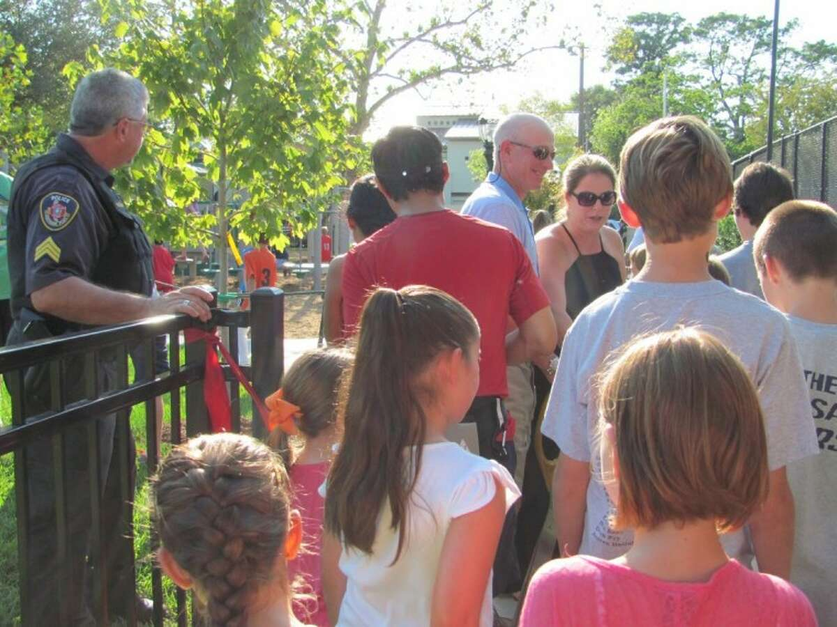 Bob and Marcie Zlotnik, center, welcome Southside Place youth to Fire Truck Park after cutting the ribbon on the park's all-new playground.