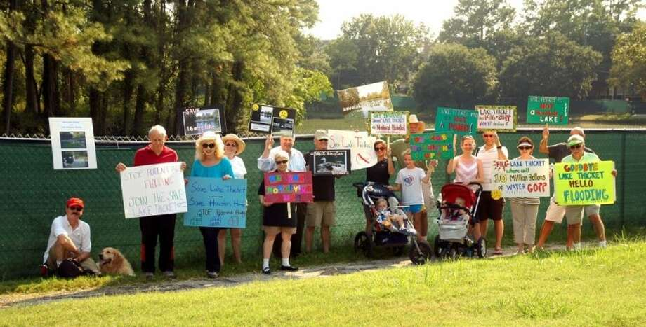 Memorial Thicket residents Sunday at an impromptu rally to save what they call Lake Thicket, behind the fence.