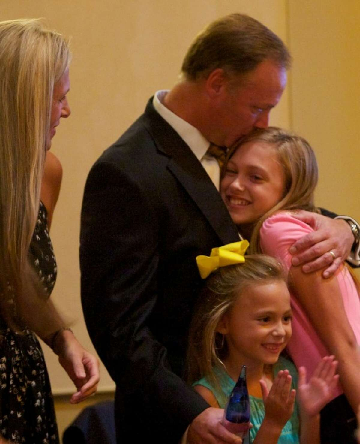 Danny Schroder receives a hug from his daughter Maddie after being named 2012 Volunteer of the Year at the South Montgomery County Chamber of Commerce Annual Awards Luncheon at The Woodlands Waterway Marriott last week.