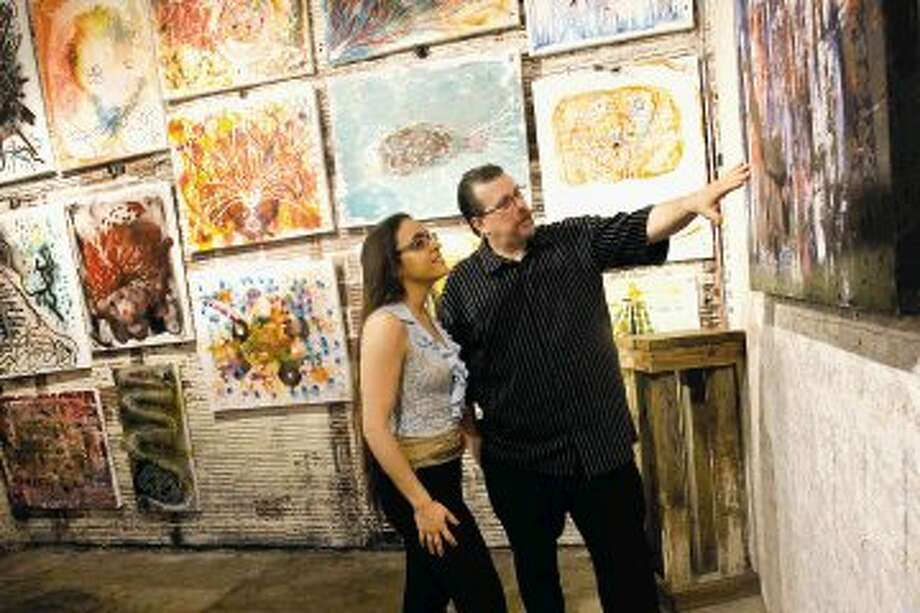JoMar owners Mark Roden and Joana Esteves discuss one of Mark's recent paintings. Photo: AMANDA J. CAIN The Observer