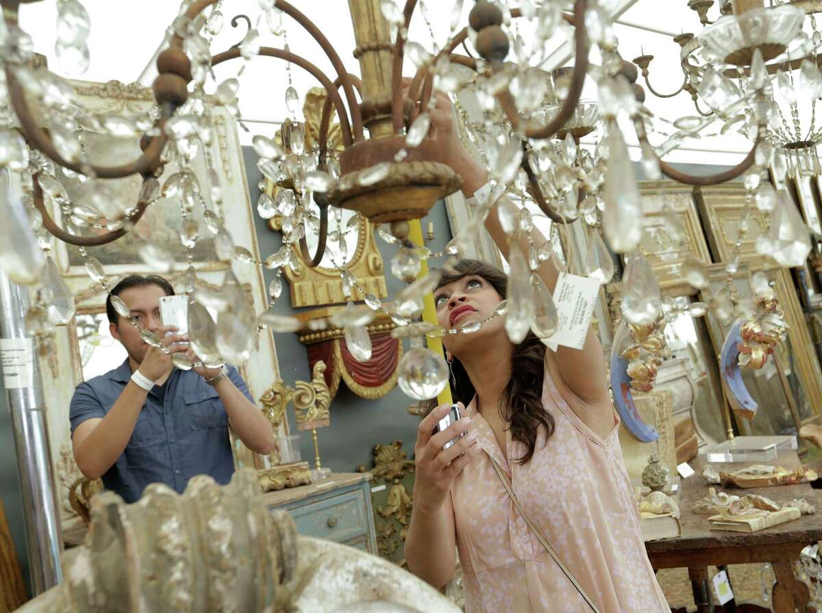 Amitha Vermameasures a chandelier while antique hunting at Marburger Farm Antique Show.
