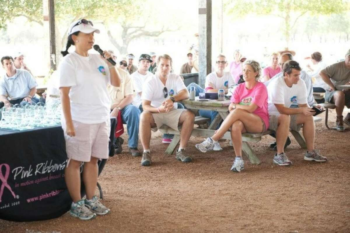 Loubel Galik, executive director of Pink Ribbons Project, speaks to the crowd at the first annual Pink Pigeon Shootout last year. Sitting from left to right is Clint Midgett, Rachel Midgett and Nathan Bane, who created the clay shooting event to help raise funds to support Pink Ribbons Project activities.