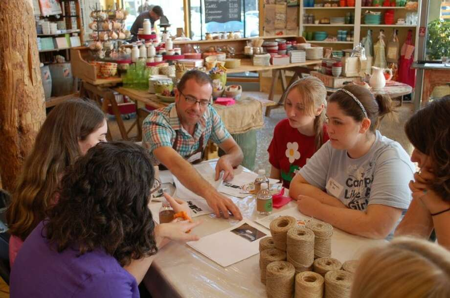 Girl Scouts Hanna C. and Tiffany B. listen tentatively as Brian Sensabaugh, display coordinator for Anthropologie, explains the inspiration behind the Highland Village store's fall window display.