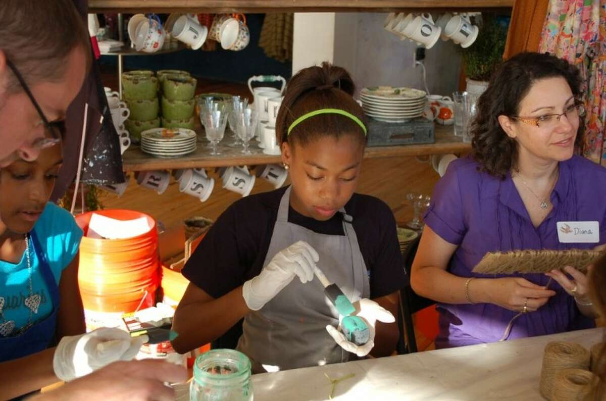 Milan P., a Senior-level Girl Scout hand paints a personalized rock for the Anthropologie store in Highland Village.