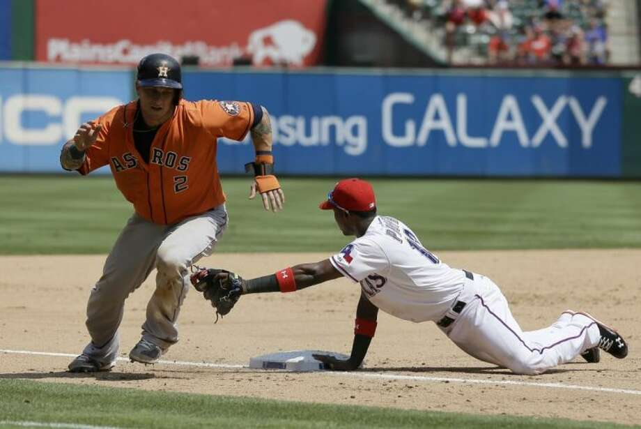 The Astros' Brandon Barnes sprints home after a botched pickoff attempt as the Rangers' Jurickson Profar follows the throw from catcher A.J. Pierzynski.