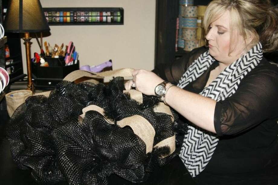 Bienvenue Designs owner Leslee Pesak begins to work on a new wreath for a customer at her home.