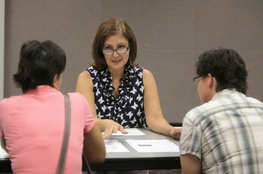 In this file photo, Diana Miller (center) talks with Victoria Mora (left) and Kristie Salter (right) from Sugar Land about the petition signing to limit multifamily developments during a petition signing event held at First Colony Branch Library in Sugar Land on Saturday, Aug. 11. Photo: File Photo By Alan Warren