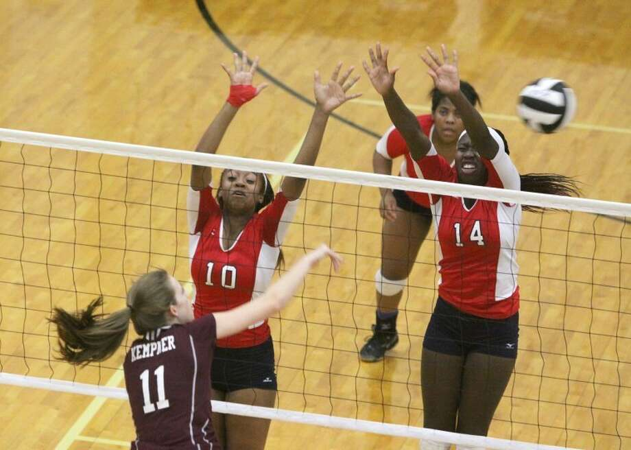 Kempner's Samantha Buller spikes over Dulles' Alexis Applewhite and Abolanie Onipede during their District 23-5A match Oct. 2 at Buddy Hopson Field House in Missouri City. Dulles won in four games to improve to 8-0 in league play.
