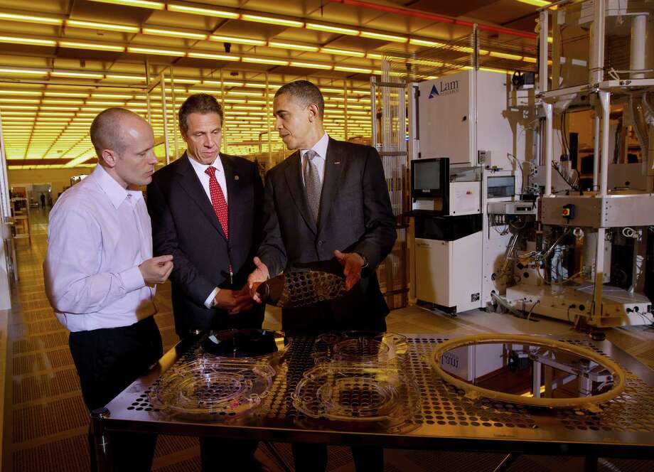 President Barack Obama, accompanied by New York Gov. Andrew Cuomo, center, holds a silicon wafer, as they tour the College of Nanoscale Science and Engineering at State University of New York at Albany's Nano-Tech complex, Tuesday, May 8, 2012, in Albany, N.Y., with Chris Borst, assistant V.P. for Engineering and Integration. Photo: Pablo Martinez Monsivais, AP / AP