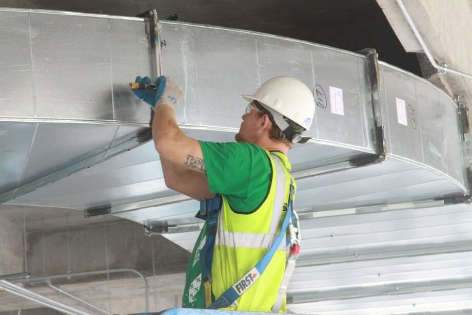 A worker installs some of the ductwork for air conditioning for Building 4 at Research Forest Lakeside.