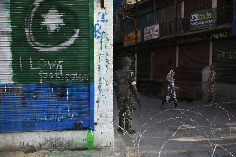 A graffiti supporting Pakistan is seen on left as a Kashmiri girl walks past Indian paramilitary soldiers near a temporary check point in Srinagar, Indian controlled Kashmir, Photo: Dar Yasin, Associated Press