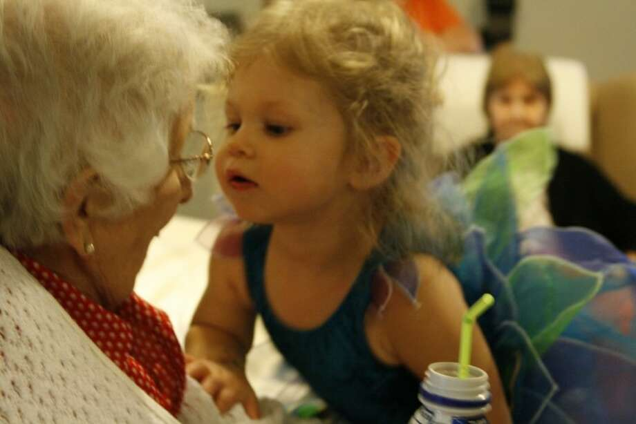 """Kyla Koch leans in to give a kiss to an """"adopted grandparent"""" at the Baby Buddies Oct. 3 celebration for Halloween."""