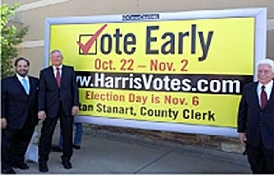 Showing off a half-size early voting billboard design are, from left, Clear Channel VP Lee Vela, Commissioner Steve Radack and County Clerk Stan Stanart. A partnership with Clear Channel will help the county promote early voting, which starts Oct. 22. Photo: Submitted Photo
