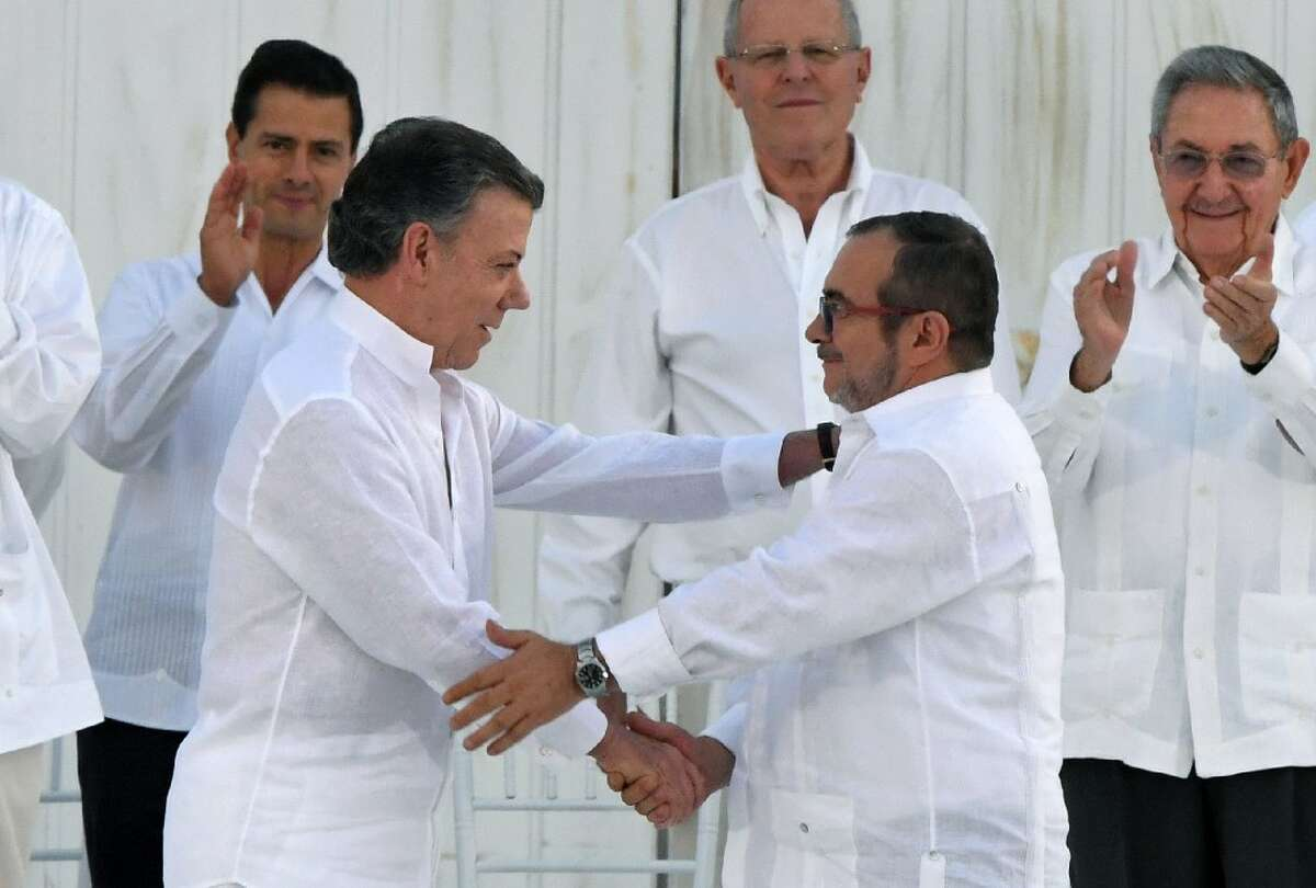 Colombian President Juan Manuel Santos (2-L) and Timoleon Jimenez,the head of the FARC,shake handsin Cartagena, Colombia on Sept. 26, 2016during the signing of the historic peace agreement between the Colombian government and the FARC.