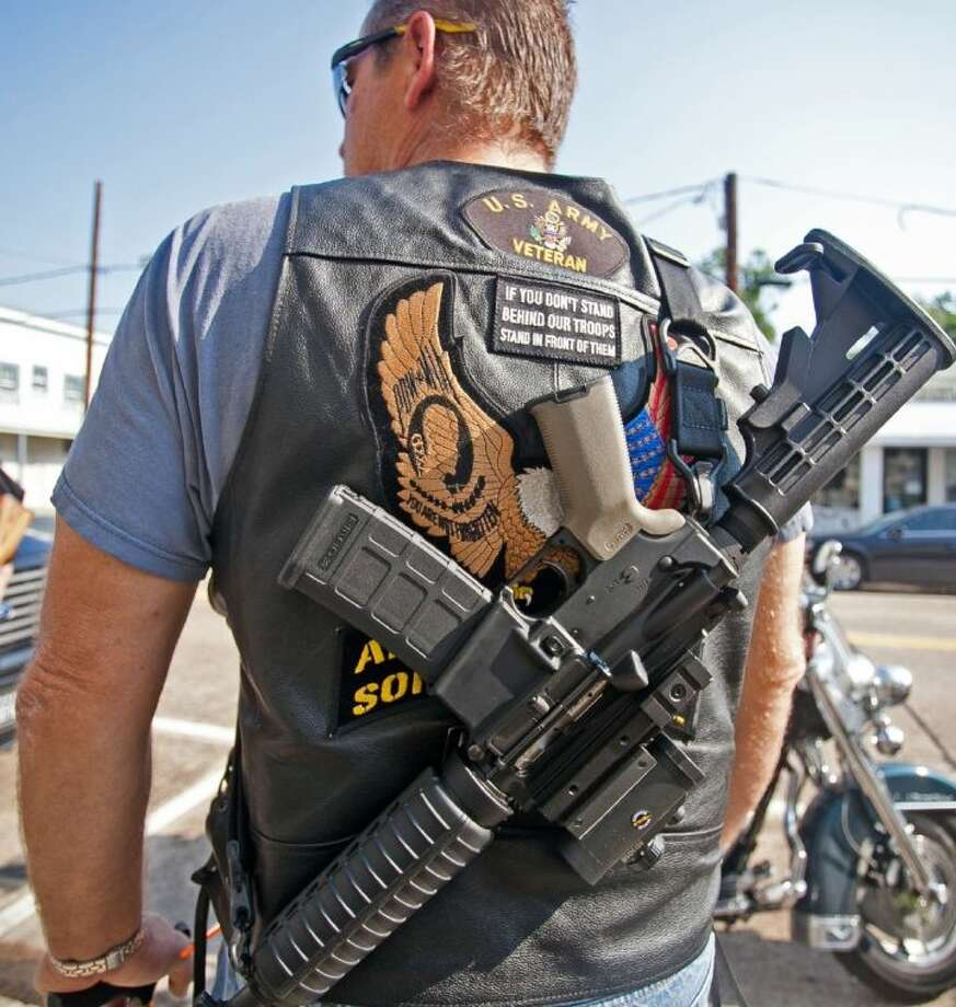 Chris Bryan shows off his AR-15 riffle at the Open Carry demonstration in Humble Aug. 17, 2013.