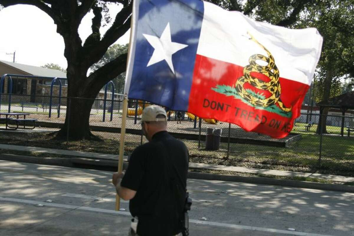 """Scott Gibbons carries a """"Don't Tread on Me"""" flag while expressing his Second Amendment rights during the Come and Take It Kingwood's Open Carry Demonstration Aug. 17, 2013."""