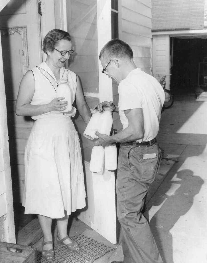 Home delivery is a time saving convenience to the busy housewife who would otherwise have to make countless trips to the store for milk. Shown here is Mrs. Joseph Ivan, 4101 Jefferson Ave., as she receives the morning milk from Howard Stickley of City Dairy. July 1954 Photo: Daily News File Photo