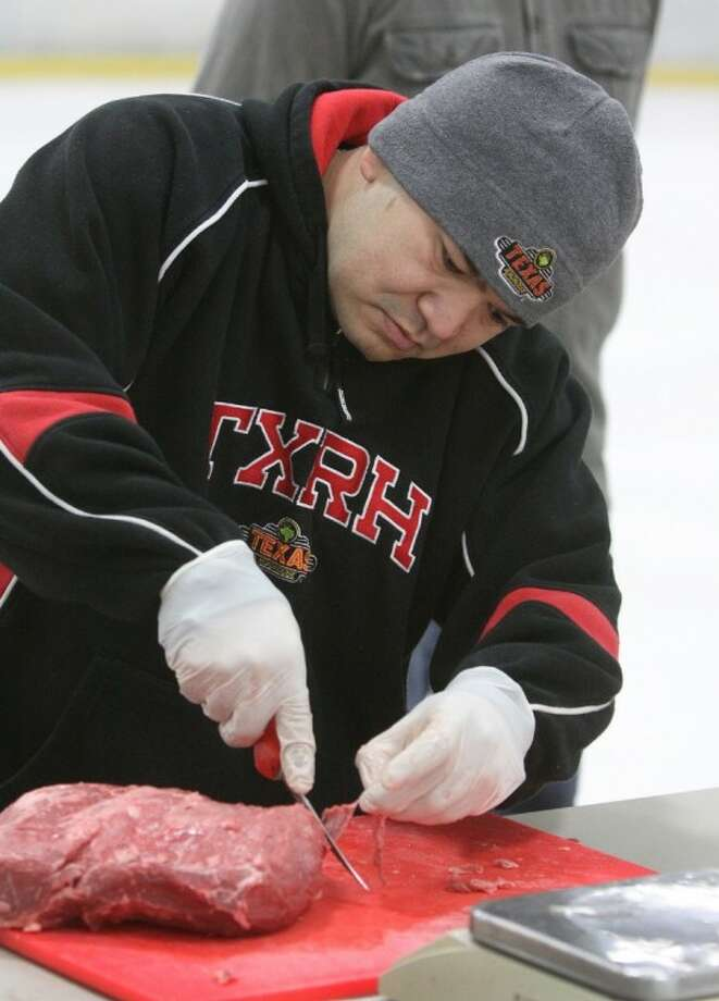 Texas Roadhouse's Eris Guevara of Katy trims up his top sirloin during the Regional Meat Cutting Competition on the ice at the Sugar Land Ice & Sports Center on Wednesday, Oct. 3.