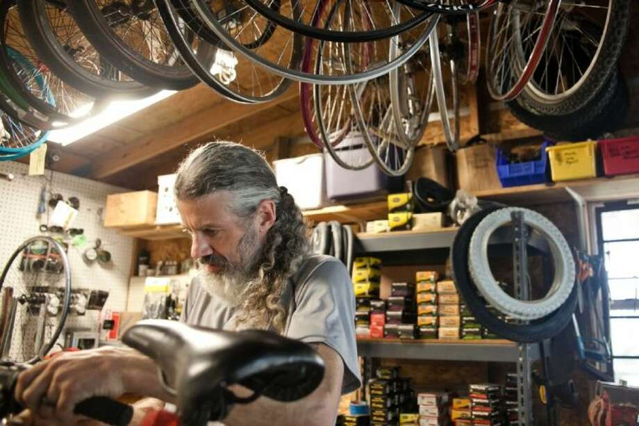 Matthew Morrison concentrates on fixing a part on bike in his shop at Sprockets Bicycles and More.