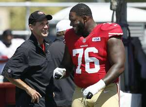 San Francisco 49ers general manager Trent Baalke, left, talks with offensive tackle Anthony Davis at an NFL football training camp in Santa Clara, Calif., Thursday, Aug. 2, 2012. (AP Photo/Jeff Chiu)