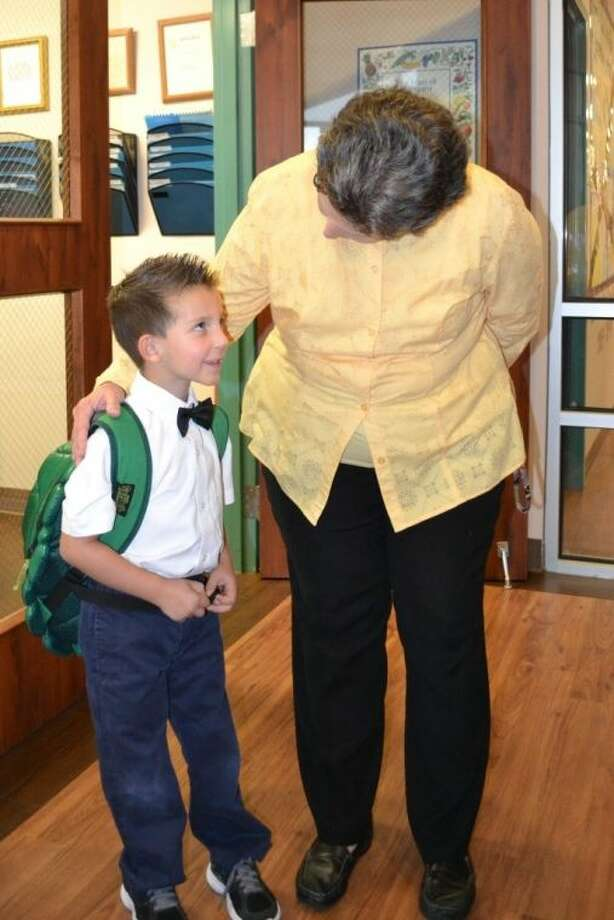 St. Anne's Principal Margaret Morgan welcomes Bennet Rica for his first day of first grade.