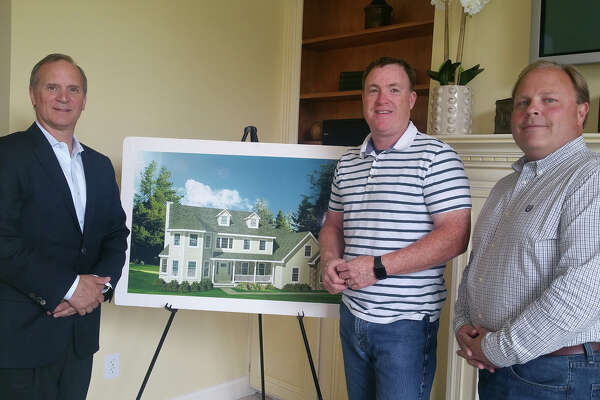 Paul Scalzo, Joseph Enright and David Dillman of Westchester Modular Homes of Fairfield County stand in front of a photo of a sample home at their Bethel offices.