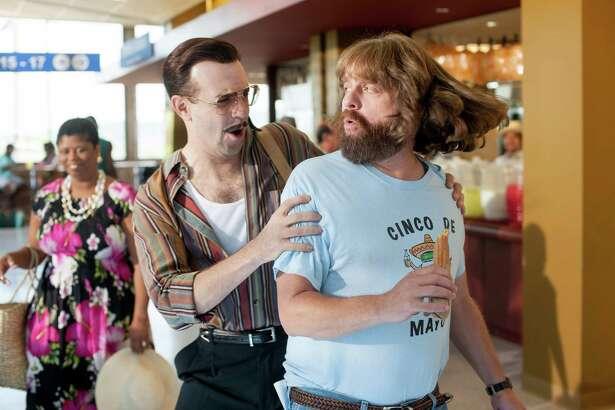 "Jason Sudekis (left) is a hit man on Zach Galifianakis' trail in the film ""Masterminds."""