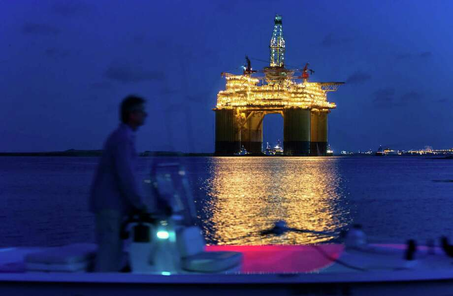 A boater passes the Royal Dutch Shell Plc Olympus tension leg platform (TLP) at dawn as it sets sail from Kiewit Offshore Services in Ingleside, Texas, U.S., on Saturday, July 13, 2013. Olympus, Shell's biggest constructed tension leg platform, started the ten day, 425-mile voyage to Mars B Field in the Gulf of Mexico on July 13. Photographer: Eddie Seal/Bloomberg Photo: Eddie Seal / © 2013 Bloomberg Finance LP