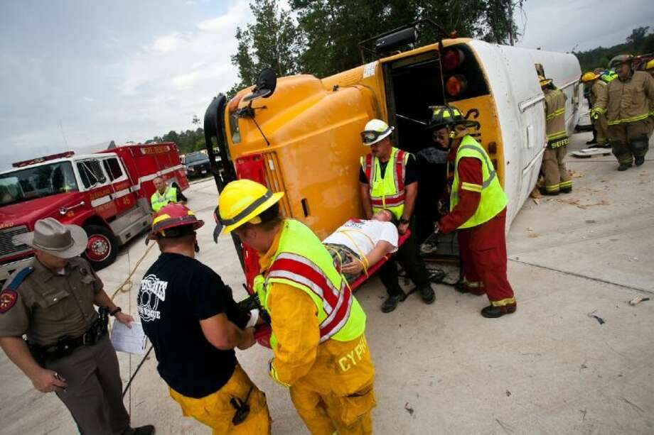 Emergency responders carry out one of the 'injured' in the Cleveland ISD bus drill, held on Aug. 14. Photo: AMANDA J.CAIN