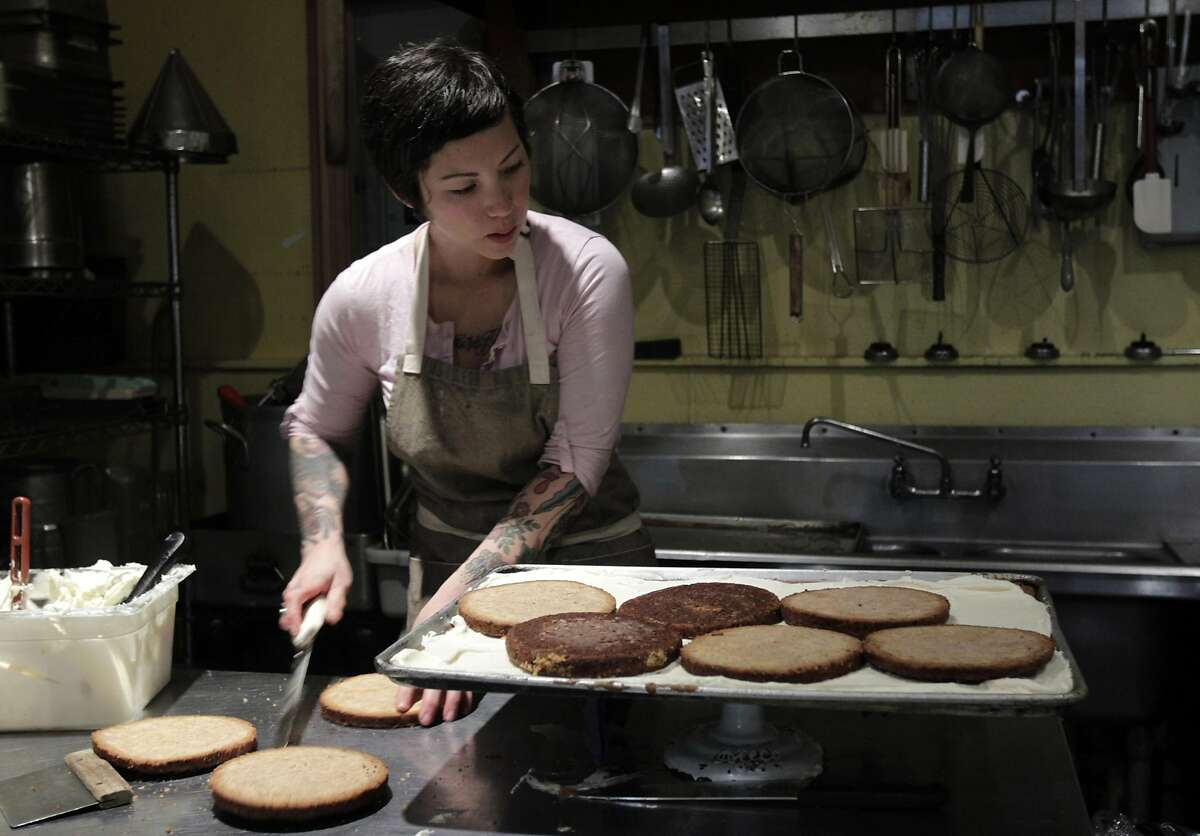 Pinkie's Bakery owner Cheryl Storms slices into carrot cake in San Francisco, Calif. on Tuesday, April 1, 2014. The bakery uses the data collected from the analytics provided by the Square payment system to streamline it's business.