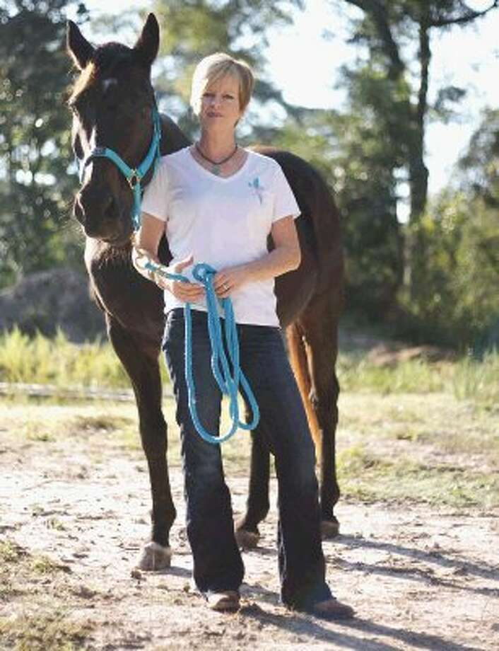 Breast cancer survivor Amy Hauser stands with Zorro at the Panther Creek Inspiration Ranch. Hauser runs the ministry Horses-Healing-Hope., which provides equine therapy for women who are post-treatment for breast cancer. Photo: Staff Photo By Eric Swist