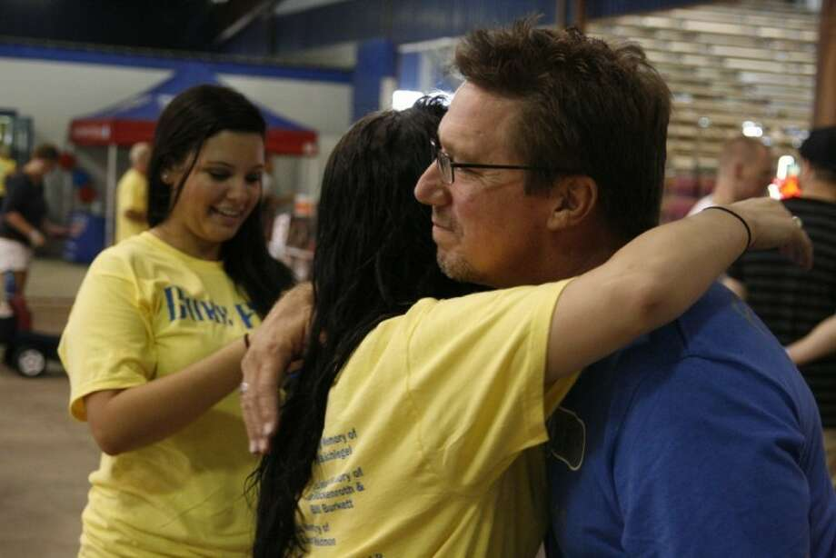 Phil Baumann receives a hug from a supporter at last year's first CureFest. This year's CureFest's MusicFest will be held Aug. 17, 2013.