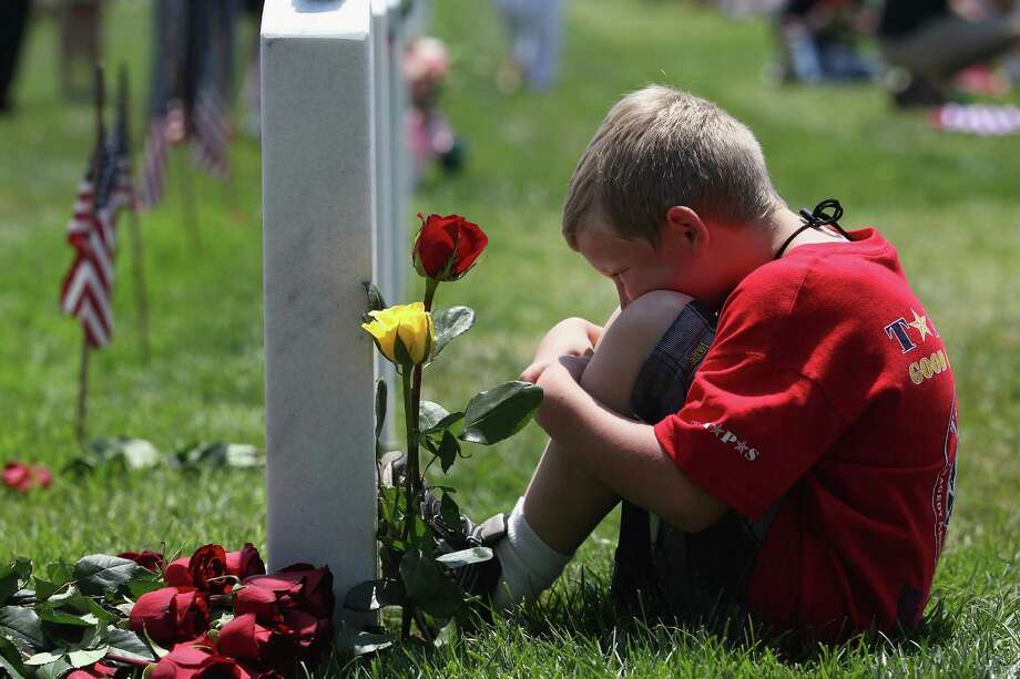 Wyatt McCain, 8, from North Pole, Alaska, looks upon his father's grave at the National Cemetery on Memorial Day on May 28, 2012 in Arlington, Virginia. His dad, Army SFC Johnathan McCain, was killed by a roadside bomb in Afghanistan in November 2011. Photo: John Moore /Getty Images / 2012 Getty Images