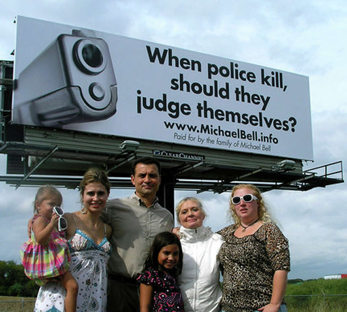 Michael Bell Sr. and his family stand near one of the billboards they bought to bring awareness to internal police investigations after Bell's son was killed.