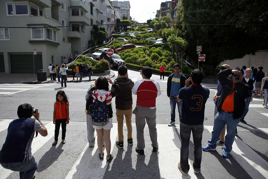 Tourists crowd into the street to take pictures of Lombard St. from Leavenworth St. in San Francisco, Calif., Saturday May 17, 2014. On Wednesday afternoon, two tourist from China were mugged of their cameras near the famed crooked section of the street. Photo: Michael Short, The Chronicle