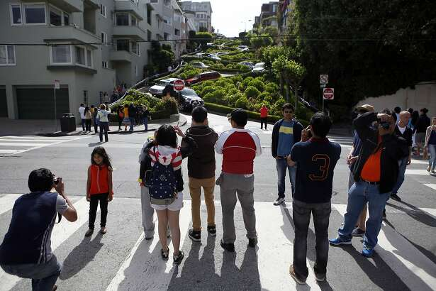 Tourists crowd into the street to take pictures of Lombard St. from Leavenworth St. in San Francisco, CA, Saturday May 17, 2014. Due to neighbor complaints of overcrowding, the SFMTA is proposing a pilot program that would shut down Lombard St. from Larkin to Leavenworth, for four weekends in the height of the summer tourist season.