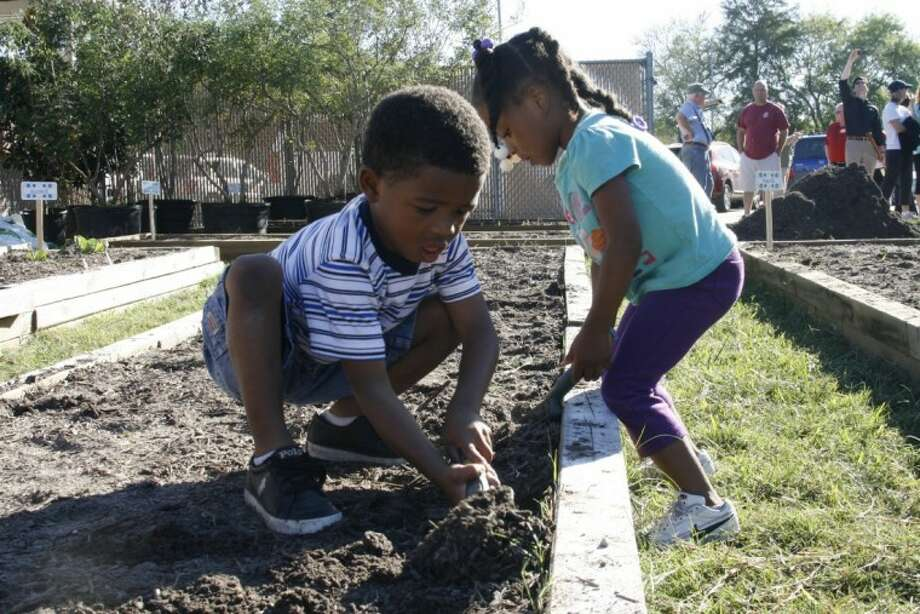 Two Lakeland Elementary students work to prune the garden at their school Oct. 19.